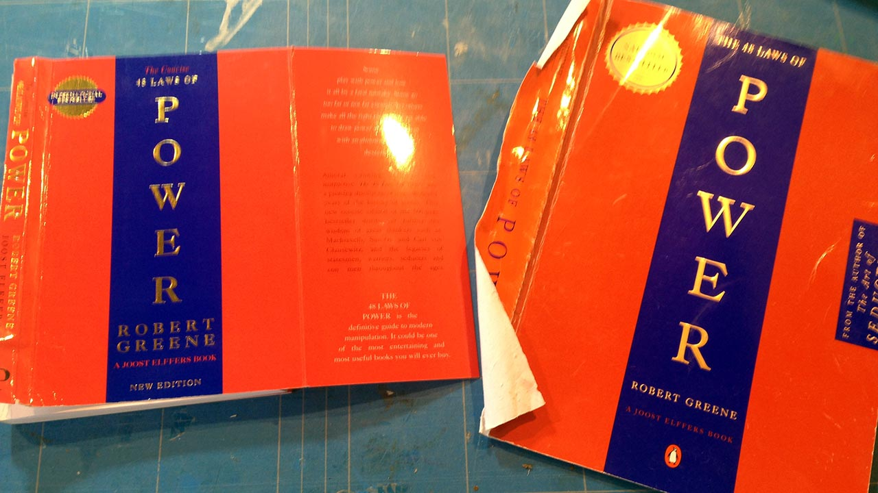 photo showing covers of Robert Greene's The 48 Laws of Power - a book I am re-working in the studio as an artwork