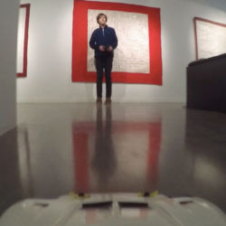 teenager in art gallery driving remote control drift car as alternative exhibition tour guide