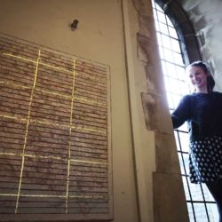 image of research fellow and project manager Chloe McKenzie at the window of Holy Trinity Chapel in Swansea installing the St Thomas Way exhibition Medieval and Modern Journeys